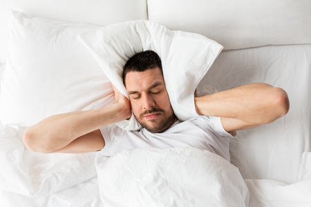 man in bed with pillow suffering from noise photo