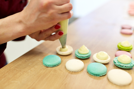 chef with injector squeezing filling to macarons Stock Photo