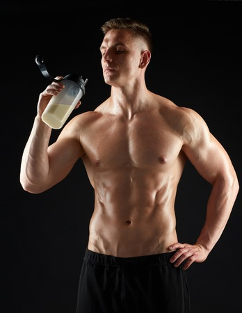 young man or bodybuilder with protein shake bottle Stock Photo