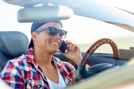young man driving car and calling on smartphone