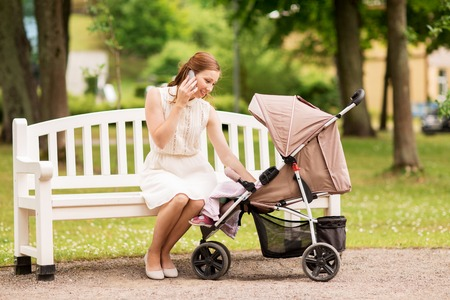 motherhood, technology and people concept - happy mother with baby girl in stroller calling on smartphone at summer park