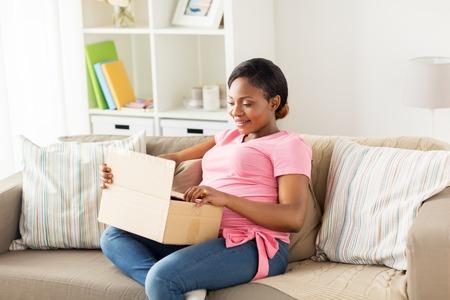 levering, mensen en zwangerschapsconcept - gelukkige zwangere Afrikaanse Amerikaanse vrouw met pakketdoos thuis