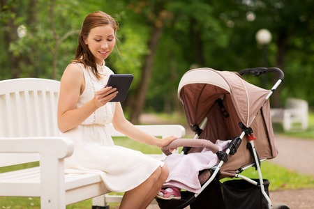 motherhood, technology and people concept - happy mother with tablet pc computer or e-book reader and baby girl stroller at summer park Stock Photo