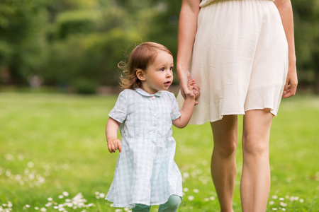 family, childhood and parenthood concept - mother with little baby girl walking at summer park Stock Photo