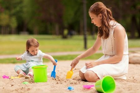 Gelukkige moeder en baby meisje spelen in zandbak