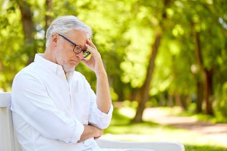 doordachte senior man zittend op zomer park Stockfoto