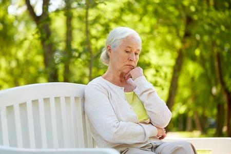 sad senior woman sitting on bench at summer park Stock Photo