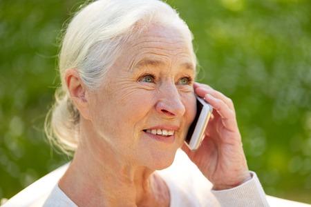 夏のスマート フォンで呼び出す幸せな年配の女性