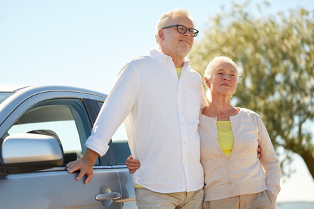 happy senior couple hugging at car in summer photo