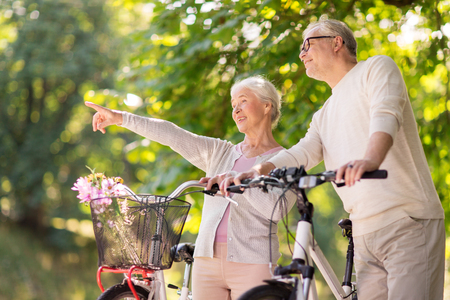 happy senior couple with bicycles at summer park Stock Photo