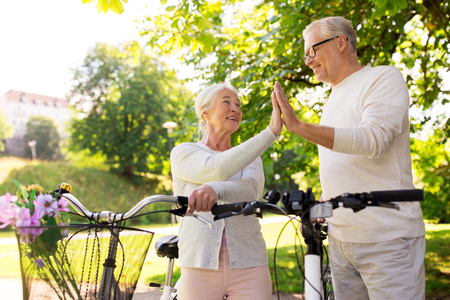 senior couple with bikes making high five at park photo