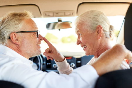 happy senior couple driving in car photo