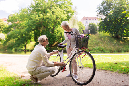 happy senior couple with bicycle at summer park photo