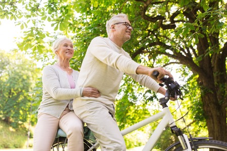 happy senior couple riding on bicycle at park photo