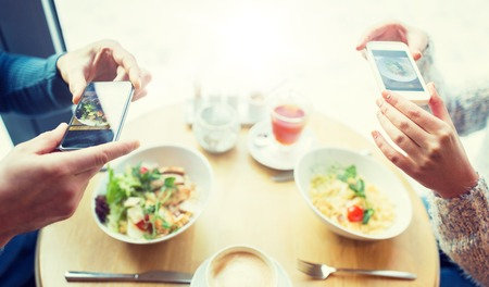 close up of couple picturing food by smartphone Stock fotó - 84435263