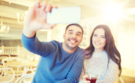 couple taking smartphone selfie at cafe restaurant photo