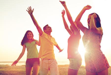 夏のビーチの上でダンスと友達に笑顔 写真素材