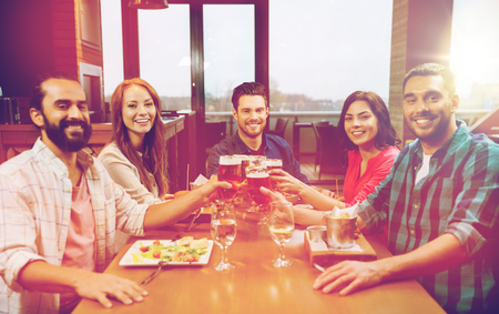 friends dining and drinking beer at restaurant photo