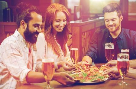 Amici mangiare pizza con birra al ristorante Archivio Fotografico - 84443920