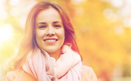 beautiful happy young woman smiling in autumn park photo