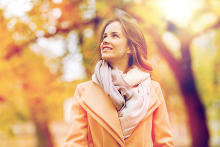 beautiful happy young woman walking in autumn park photo