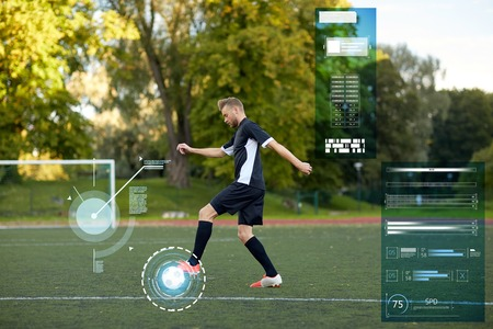 sport, technology and people concept - soccer player playing with ball on football field Reklamní fotografie - 84365349