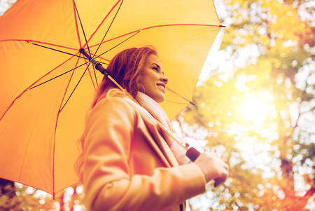 happy woman with umbrella walking in autumn park photo