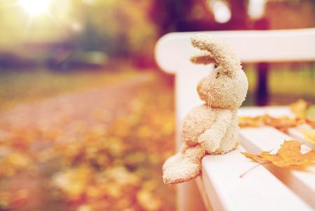 Seizoen, jeugd en eenzaamheid concept - eenzame speelgoed konijn op bankje in de herfst park Stockfoto - 84365388