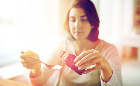 healthcare, people and medicine concept - woman pouring medication or antipyretic syrup from bottle to spoon