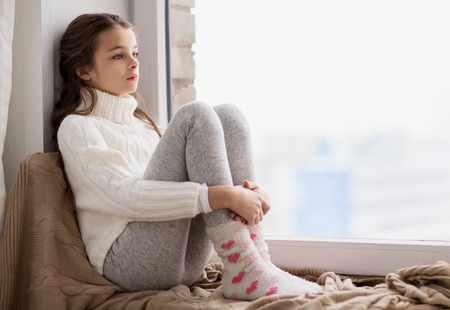 childhood, sadness and people concept - sad beautiful girl in sweater sitting on sill at home window in winter Фото со стока - 84365460