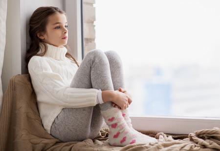 Infanzia, tristezza e gente concetto - triste bella ragazza in maglione seduto sul davanzale a casa finestra in inverno Archivio Fotografico - 84365460