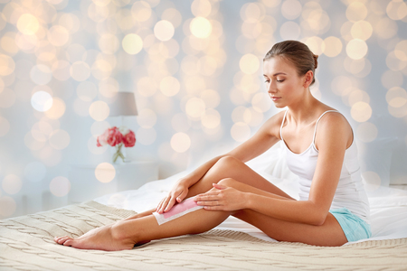 beauty, hair removal and people concept - beautiful woman applying depilatory wax strip to her leg skin at home bedroom