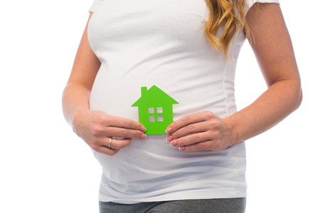 pregnancy, ecology, people and housing concept - close up of pregnant woman with green house icon Stock Photo