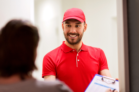 deliverer: delivery, mail, people and shipping concept - happy man with clipboard and customer signing form at home