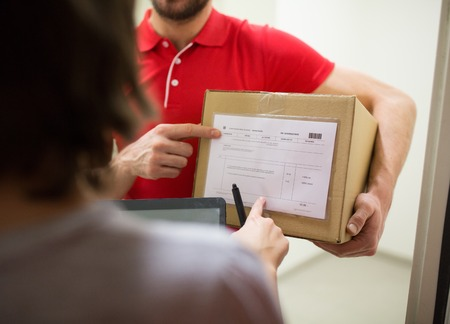home delivery service, mail, people and shipping concept - man delivering parcel box to customer with tablet pc computer