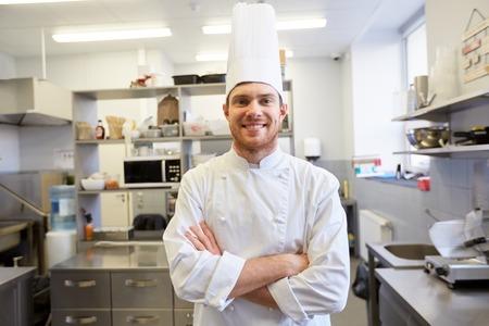 koken, beroep en mensenconcept - Gelukkige mannelijke chef-kok in toque met gekruiste handen in restaurantkeuken Stockfoto
