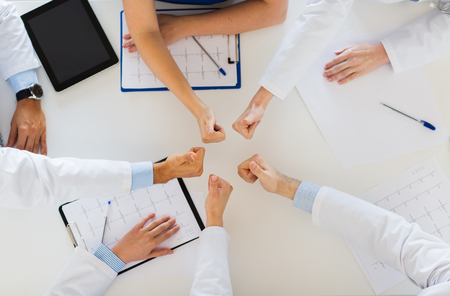 medicine, healthcare and success concept - group of doctors with cardiograms, clipboards and tablet pc computer showing thumbs up over table at hospital