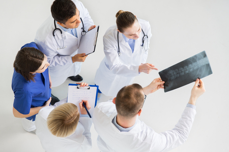 medicine, healthcare and surgery concept - group of doctors or surgeons with spine x-ray and clipboards at hospital
