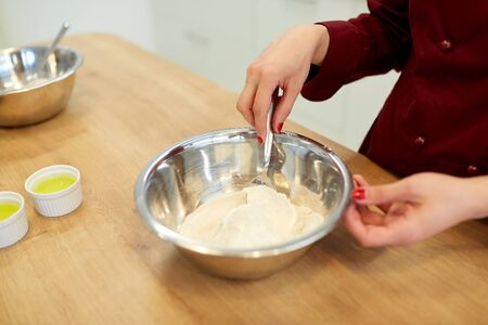 cooking food, baking and people concept - chef with flour in bowl making batter or dough Reklamní fotografie - 84365778