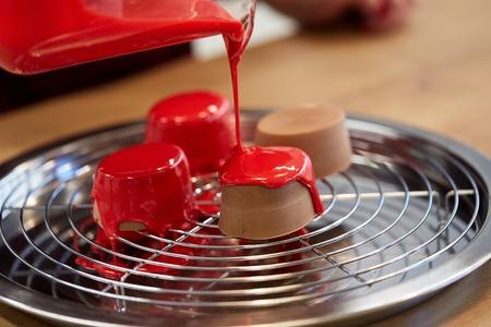 Concept de cuisine, de pâtisserie et de nourriture - verseuse glaçant des gâteaux au chocolat sur un plateau avec grille à la pâtisserie Banque d'images - 84365781