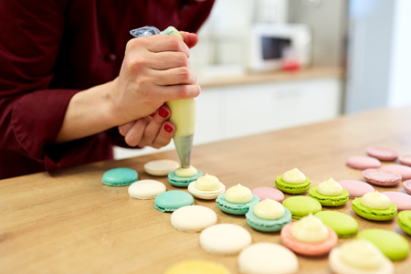 cooking, food and baking concept - chef with confectionery bag squeezing cream filling to macarons shells at pastry shop kitchen
