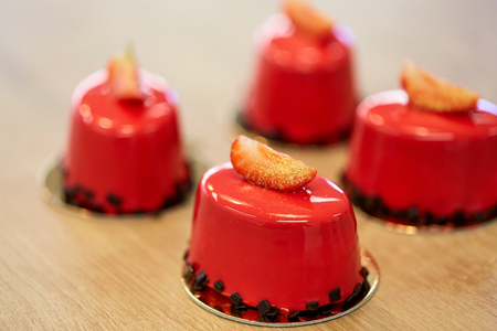 cooking, baking and food concept - strawberry mirror glaze cakes with edible gold at confectionery
