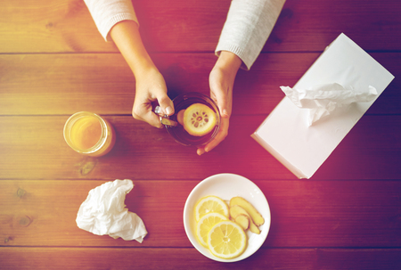ill woman drinking tea with lemon and ginger Imagens
