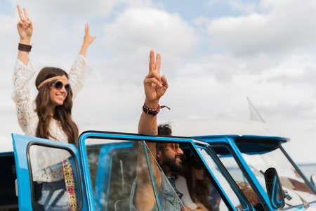 hippie friends at minivan car showing peace sign Stock Photo