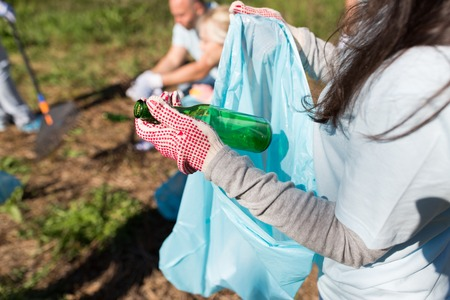 volunteer with trash bag and bottle cleaning area Stock Photo