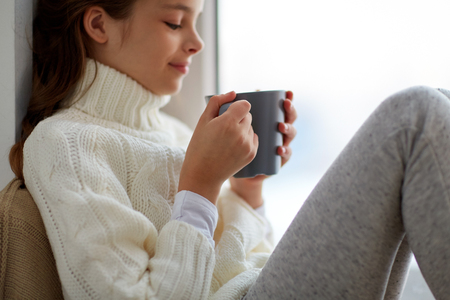 girl with tea mug sitting at home window Banco de Imagens