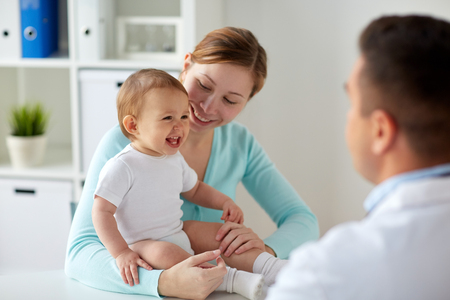 happy woman with baby and doctor at clinic Foto de archivo