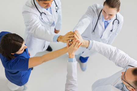 group of doctors making high five at hospital