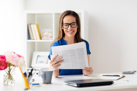 gelukkige vrouw die in glazen krant op kantoor leest Stockfoto