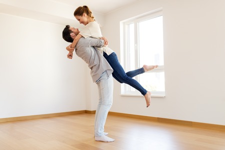 happy couple at empty room of new home Imagens